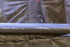 Black painted tube on the background of black stretched fabric stock photo