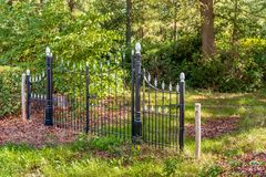 Black painted wrought-iron gate in a park. Next to the closed gate is a fence made of wooden poles and barbed wire. It is a sunny day at the end of the summer royalty free stock image