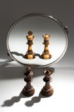 A black pair of a king and queen is looking in a mirror to see themselves as a black and white colored pair. A pair of a black king and a black queen chess Royalty Free Stock Photos