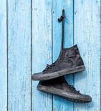 Black pair of worn men`s textile sneakers hangs. On the old blue wooden background royalty free stock images