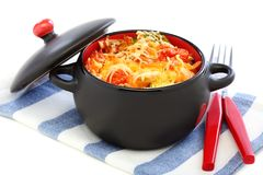 Black pan with sauteed vegetables and cheese. Stock Photos
