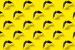 Black paper bat pattern with falling shadow on yellow background. Halloween decorations. Halloween concept. Flat lay stock photos