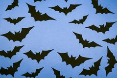 Black paper bats on a blue background. Halloween background, flat lay Stock Photography