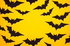 Black paper bats on an orange background. Halloween background, flat lay Royalty Free Stock Image
