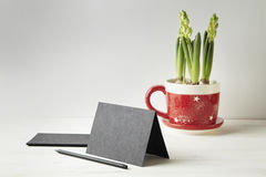 Black paper card or postcard on white wooden table, space for layout. Flowers in red pot.  Royalty Free Stock Photography