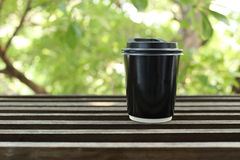 Black paper coffee cup on wooden with green leaves background. Black paper coffee cup on a wooden with green leaves background Royalty Free Stock Photo