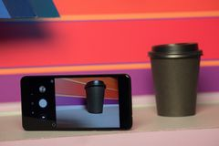 Black paper Cup with plastic lid. coffee or takeaway on a violet and pink background. brutal glass with mobile phone stock image