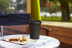 Black paper disposable cup of coffee to takeaway on marble table in garden outside cafe. Breakfast morning on air. Royalty Free Stock Images