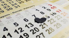 Black paper heart covers number 14 in February on the calendar. Valentine`s day, love and broken heart. Black paper heart covers number 14 in February on the stock footage