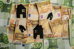 Black paper houses with euro banknotes in background.  Stock Image