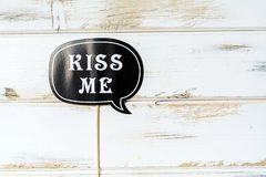 Kiss Me Paper Party Accessory. Black Paper Kiss me note.Party accessory Stock Photo