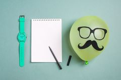 Black paper mustache and glasses on balloon and a notepad with a felt-tip pen stock image
