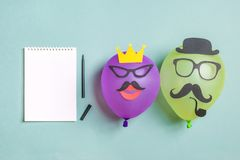 Black paper mustache and glasses on balloon and a notepad with a felt-tip pen royalty free stock images