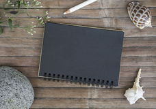Black paper notebook on rustic wooden background with natural decor. Black notepad with blank page. Lettering or art mockup. Shabby chic banner template Royalty Free Stock Photo