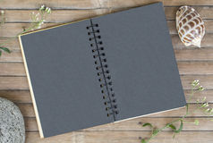 Black paper notebook on rustic wooden background with natural decor. Black notepad with blank page. Rustic artwork mockup. Shabby chic banner template. Vintage Royalty Free Stock Photo