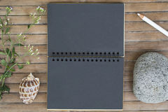 Black paper notebook on rustic wooden background with natural decor. Black notepad with blank page. Vertical spread mockup. Shabby chic banner template Stock Photography