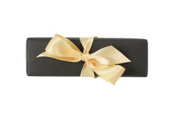 Black paper rectangle giftbox with champagne ribbon bow isolated Stock Photo