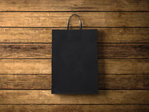 Black paper shopping bag on the wooden background. In focus. Horizontal. 3d render Stock Image
