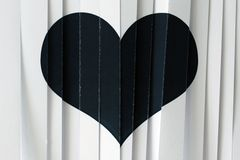 Black papper heart. Black heart on the white cut papper card Stock Photo