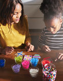 Black parent and child making beaded objects Royalty Free Stock Photo