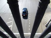 Black passenger car drove out from under the bridge. Photography over the bridge railing top stock image