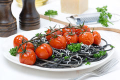 Black pasta with baked tomatoes and parsley Stock Image