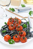 Black pasta with baked tomatoes and parsley, vertical Royalty Free Stock Photos