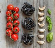 Black pasta with cherry tomatoes, garlic and basil Stock Image