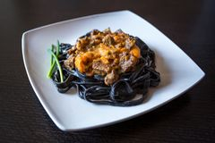 Black pasta with cuttlefish ink. Pasta of durum wheat semolina with squid ink with beef and sweet pepper sauce on a square plate royalty free stock photo