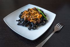 Black pasta with cuttlefish ink. Pasta of durum wheat semolina with squid ink with beef and sweet pepper sauce on a square plate stock image