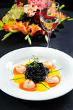 Black pasta with meat. Garnished with sauce and herbs close-up stock photo
