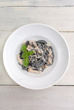 Black pasta with mushrooms and cream. In a white plate on light wooden background top view stock photography