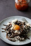 Black pasta with red pesto and egg yolk. Black squid ink pasta with sun dried tomatoes red pesto and egg yolk stock images