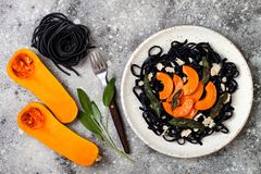 Black pasta with roasted butternut squash, parmesan cheese and fried sage. Halloween black and orange party dinner concept. Black pasta with roasted butternut Stock Photo