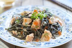 Black pasta with salmon and red caviar in cream sauce Stock Photos