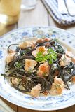 Black pasta with salmon and red caviar in cream sauce Royalty Free Stock Photography