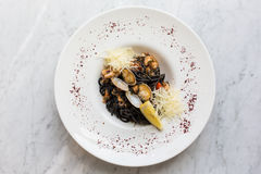 Black pasta served with seafood. Black noodles with mussels, squid, octopuses with the addition of Parmesan cheese royalty free stock image
