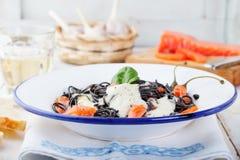 Black pasta spaghetti with cream sauce and smoked salmon Italian cuisine Stock Photos