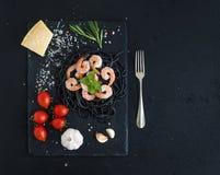Black pasta spaghetti with shrimps, basil, pesto Stock Image