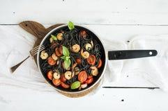 Black pasta spaghetti with shrimps, basil, pesto Royalty Free Stock Image