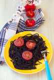 Black pasta  with tomatoes Stock Images