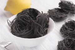 Black pasta in a white plate on a white table background stock photos