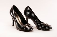 Black patent leather pumps. A pair of black and white polka dot pumps on a white background Stock Images