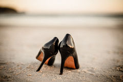 Black patent shoes at beach Stock Photos