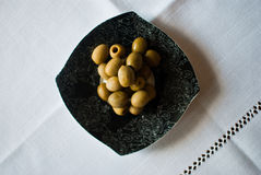 Black patterned plate with olives on the white tablecloth Stock Photo