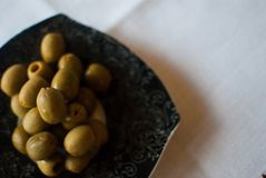 Black patterned plate with olives on the white tablecloth Stock Photos