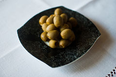 Black patterned plate with olives on the white tablecloth Stock Photography