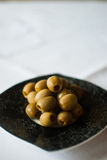 Black patterned plate with olives on the white tablecloth Royalty Free Stock Image