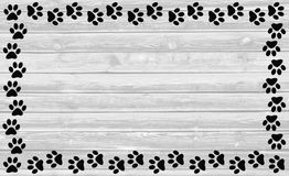 Black paw prints frame on wooden background royalty free stock image
