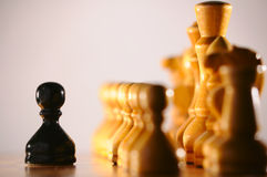 Black pawn against white chess pieces Royalty Free Stock Image